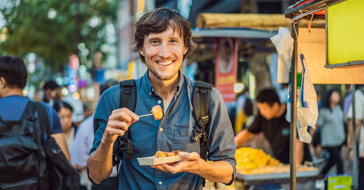 Young man tourist eating Typical Korean street food on a walking street of Seoul. Spicy fast food simply found at local Korean martket, Soul Korea