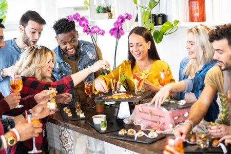 Des amis autours d'un buffet en train de manger et boire